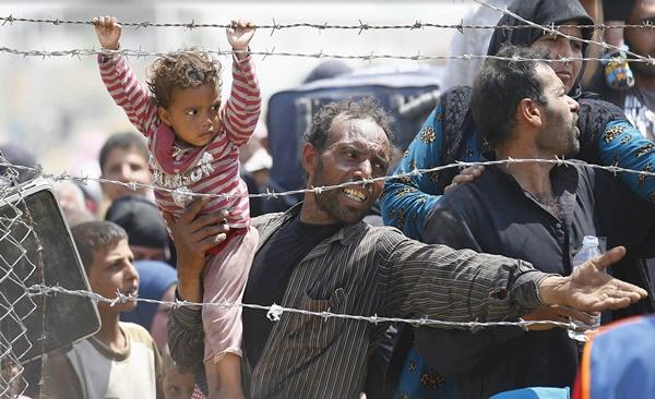 Un refugiado sirio reacciona mientras espera detrás de vallas fronterizas para cruzar a Turquía en la puerta de la frontera Akcakale en la provincia de Sanliurfa, Turquía, el 15 de junio de 2015. El domingo, las autoridades turcas reabrió la frontera después de unos días de cierre, dijo una fuente de seguridad, agregando que espera que hasta 10.000 personas a venir a través. #