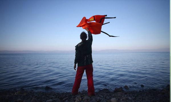 Una mujer olas un chaleco salvavidas para dirigir un barco emigrante en tierra, ya que hace el cruce de Turquía a la isla griega de Lesbos, el 12 de noviembre de 2015, en Sikaminias, Grecia. Balsas y barcos siguen haciendo el viaje desde Turquía hasta Lesbos cada día como miles de personas huyen de conflictos en Irak, Siria, Afganistán y otros países. Más de 500.000 inmigrantes han entrado en Europa lo que va del año y aproximadamente cuatro quintas partes de los han pagado de contrabando por mar a Grecia desde Turquía, la principal ruta de tránsito hacia la UE. La mayoría de los que entran en Grecia en un barco de Turquía son de las zonas de guerra de Siria, Irak y Afganistán. #