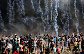A picture taken on August 17, 2018 shows tear gas canisters, thrown by Israeli forces, falling onto Palestinian protesters during a demonstration along the border of the Gaza Strip, east of Gaza City. (Photo by MAHMUD HAMS / AFP)        (Photo credit should read MAHMUD HAMS/AFP/Getty Images)