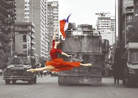 """Entre un millón de personas, una figura envuelta en tela carmín representó la paz. La bailarina Catalina Duarte ejecutó un paso de ballet con una bandera de Chile frente a dos vehículos de carabineros durante las protestas del 25 de octubre en Santiago. """"Fue un instante de paz, de calma. No había agresión. Fue un momento de respeto entre manifestantes y policías"""", cuenta a Verne María Paz Morales, la autora de esta imagen. """"Catalina es belleza y arte frente a la rudeza y la crueldad de los policías"""", señala la chilena.   La fotografía fue publicada por medios de comunicación en todo el mundo en torno a la manifestación de más de 1,2 millones de personas en la capital chilena. Morales fue acompañada del también fotógrafo Oscar Seguel para fotografiar a la bailarina como parte de un proyecto denominado Danza en la Urbe, que retrata a los bailarines en las calles."""